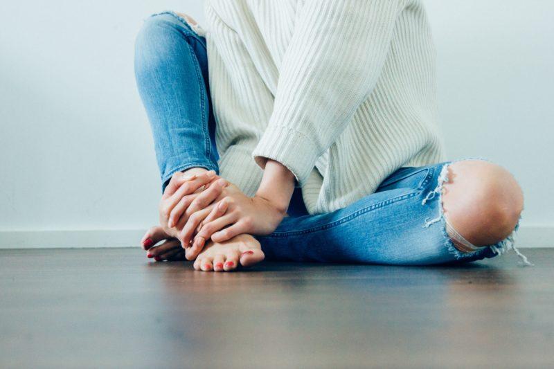 Chica descalza tocándose los pies